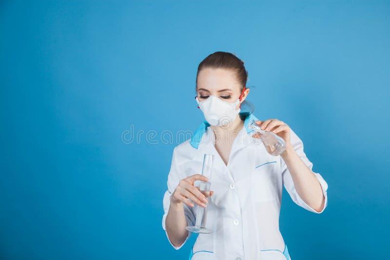 Kobieta doktor w masce ochronnej przed koronawirusem na niebieskim tle obraz royalty free