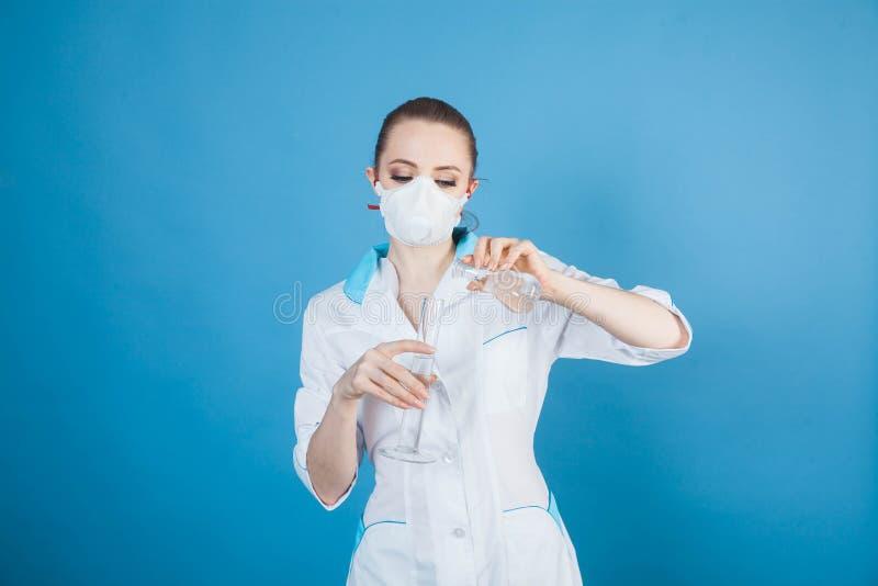 Kobieta doktor w masce ochronnej przed koronawirusem na niebieskim tle zdjęcia stock