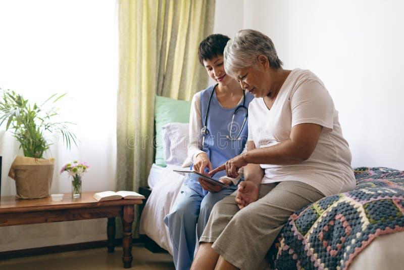 Kobieta doktorski i starszy żeński pacjent używa cyfrową pastylkę przy emerytura domem zdjęcia stock