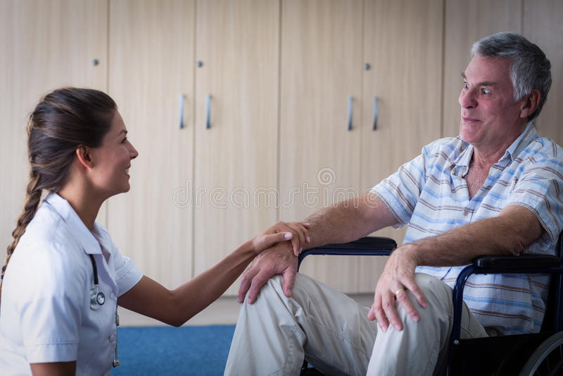 Kobieta doktorski pocieszający starszy mężczyzna w żywym pokoju obraz royalty free