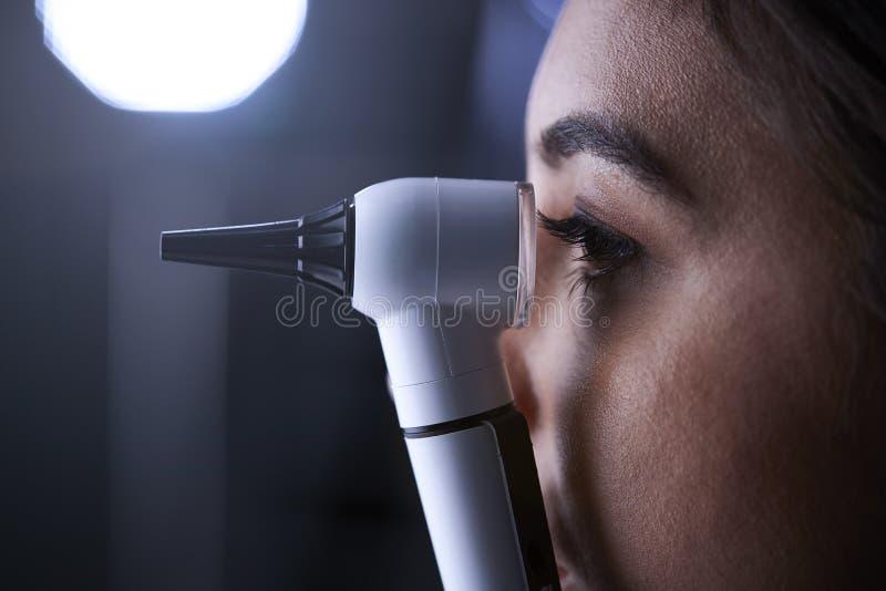 Kobieta doktorski używa otoskop dla egzaminu, boczny widok obraz royalty free
