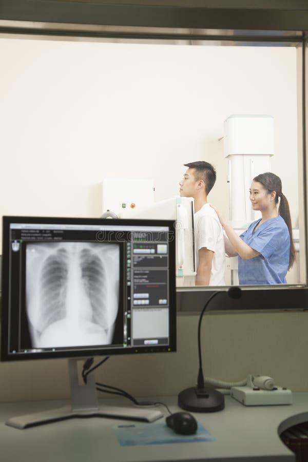 Kobieta Doktorskiego Egzamininuje Męskiego pacjenta W połowie sekcja Z Radiologiczną maszyną zdjęcia royalty free