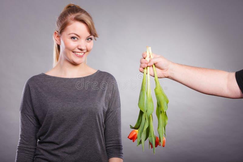 Kobieta dostaje bukiet tulipany od mężczyzna obrazy stock