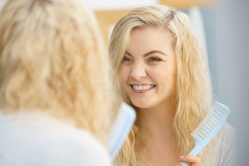 Kobieta dostaje gotowy w łazience, zgrzywiony włosy zdjęcie stock