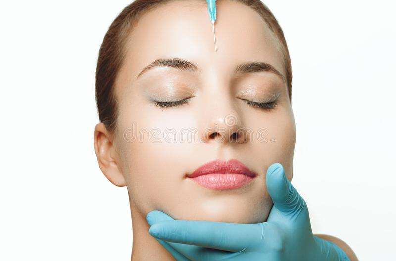 Kobieta dostaje kosmetycznego zastrzyka botox w policzku, zbliżenie zdjęcia royalty free