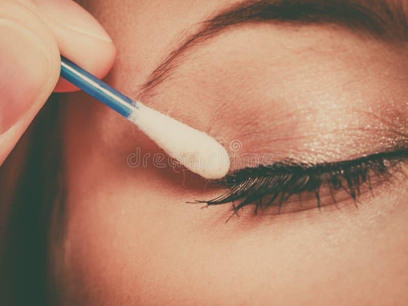 Kobieta dostaje ona makeup robić z bawełnianymi pączkami obraz stock
