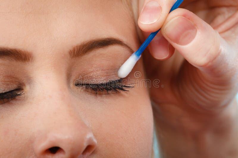 Kobieta dostaje ona makeup robić z bawełnianymi pączkami fotografia royalty free