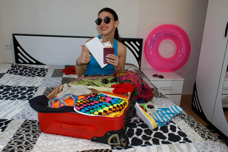 Kobieta Dostaje Przygotowywający Dla Podróżować młoda piękna kobieta, czerwona walizka, obsiadanie, czekanie, wakacje podróżuje a fotografia stock