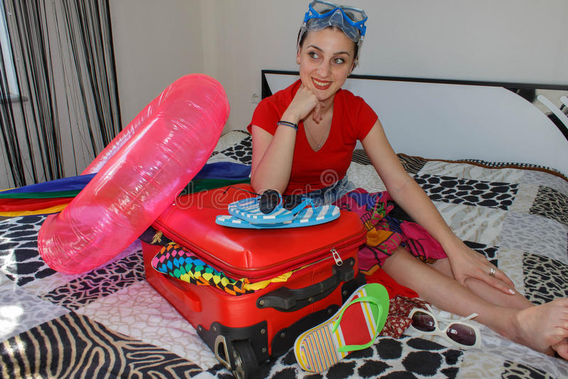Kobieta Dostaje Przygotowywający Dla Podróżować młoda piękna kobieta, czerwona walizka, obsiadanie, czekanie, wakacje podróżuje a zdjęcia stock