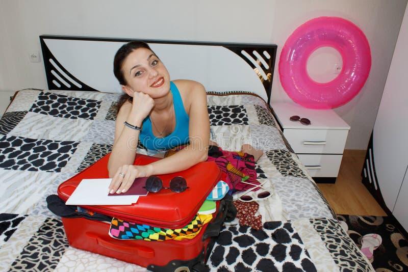 Kobieta Dostaje Przygotowywający Dla Podróżować młoda piękna kobieta, czerwona walizka, obsiadanie, czekanie, wakacje podróżuje a zdjęcia royalty free