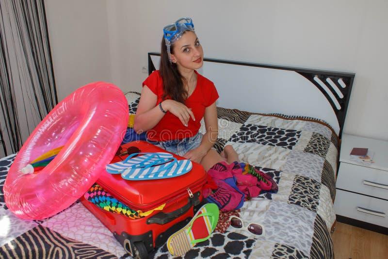 Kobieta Dostaje Przygotowywający Dla Podróżować młodego pięknego kobiety walizki czekania czerwonego siedzącego wakacje kolorowy  zdjęcia stock