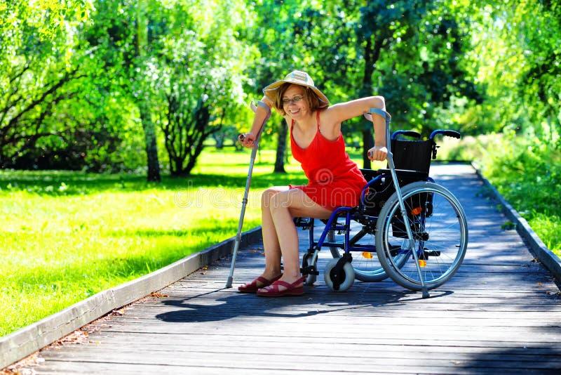 Kobieta dostaje up od wózka inwalidzkiego obraz stock