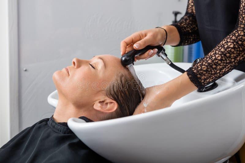 Kobieta Dostaje włosy Myjący W salonie zdjęcie royalty free