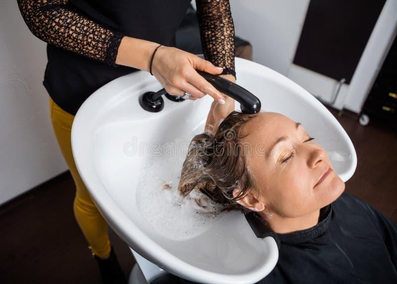 Kobieta Dostaje włosy Myjący W salonie obrazy royalty free