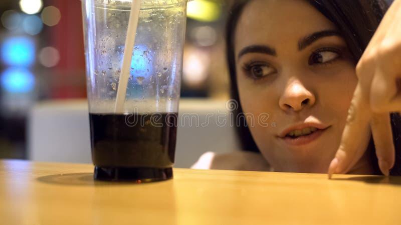Kobieta dotyka odprowadzenie plastikowy szk?o z mi?kkim napojem, cukrzyce ryzyko, cukier obraz royalty free