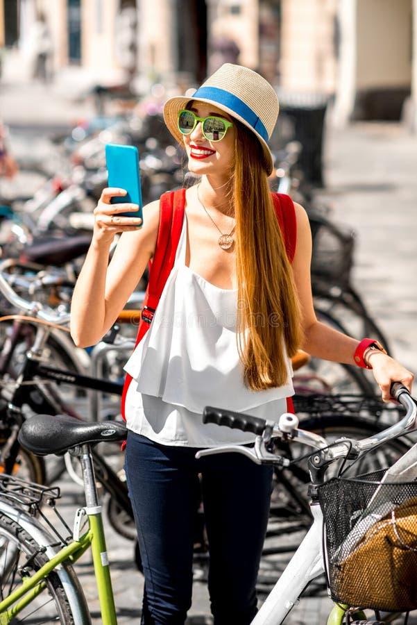 Kobieta dzierżawi bicykl z mądrze telefonem zdjęcia royalty free
