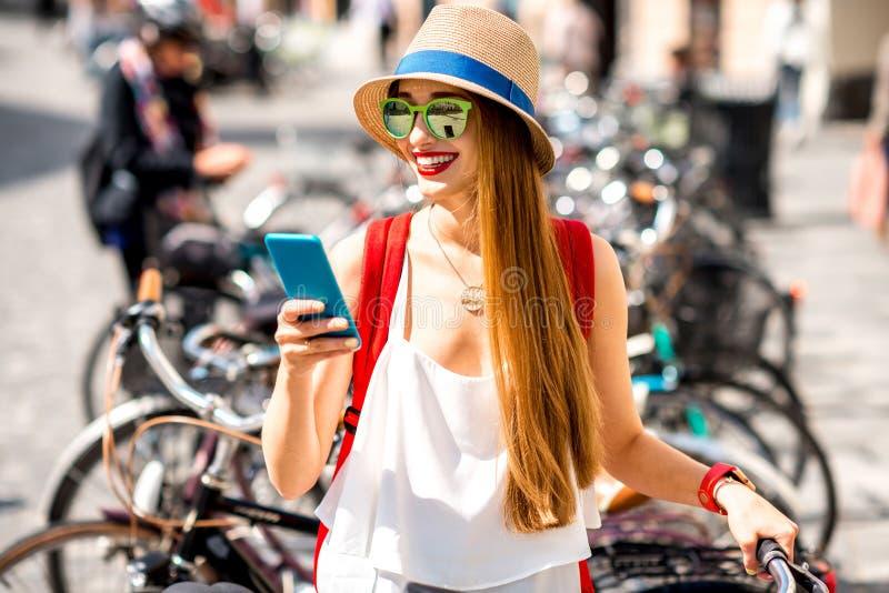 Kobieta dzierżawi bicykl z mądrze telefonem fotografia royalty free