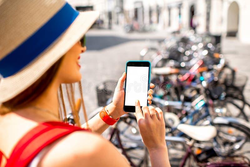 Kobieta dzierżawi bicykl z mądrze telefonem zdjęcia stock