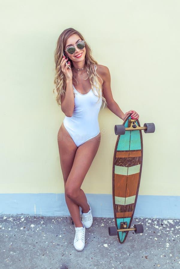 Kobieta dzwoni telefonem Szczęśliwa zabawy młoda dziewczyna, jeździć na deskorolce, longboard Modny i elegancki w białym ciała ką fotografia stock