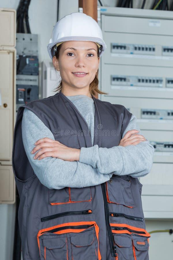 Kobieta elektryk pozuje obok panelu fotografia stock