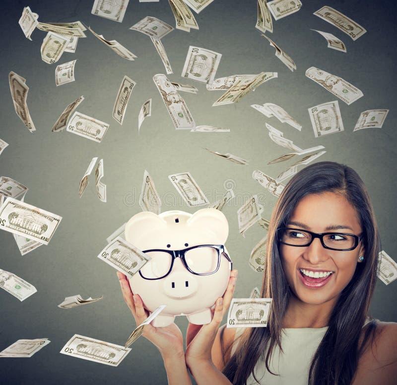 Kobieta excited nad savings pod pieniądze puszka podeszczowymi spada dolarami obraz stock