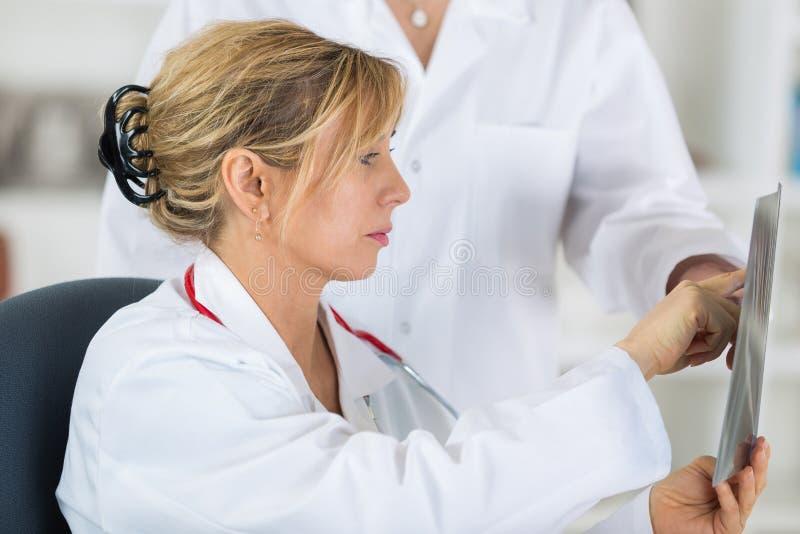 Kobieta fabrykuje patrzeć i dyskutować promieniowanie rentgenowskie wizerunek przy szpitalem obraz royalty free