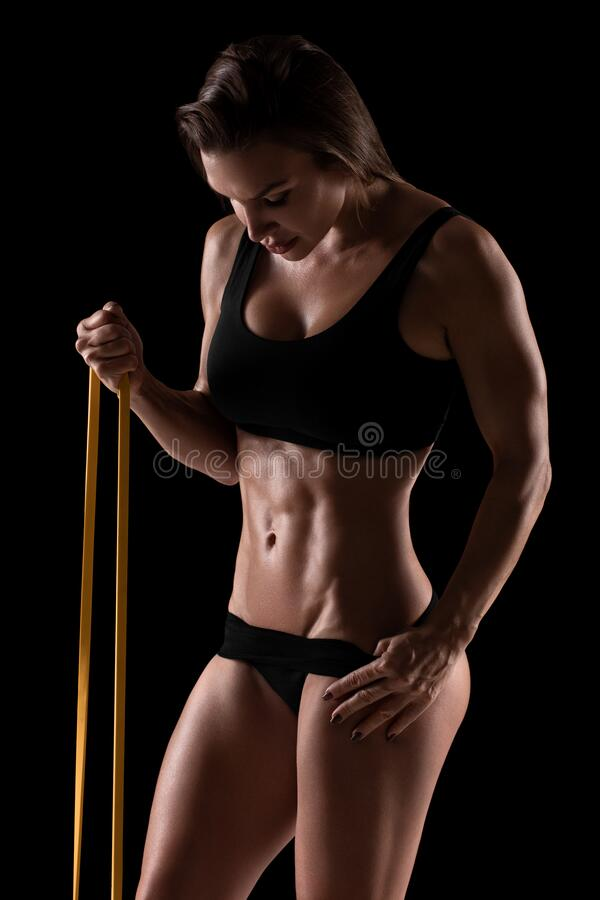 Kobieta fitness ukazująca brzuszek i płaski brzuch, odizolowana na czarnym tle Brzuch fotografia royalty free