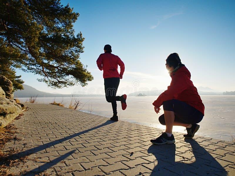 Kobieta folowing działającego mężczyzny przy jezioro plażą Drużyna biegacze fotografia stock