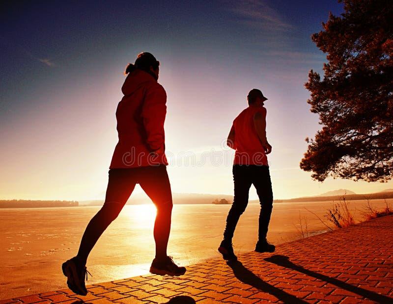Kobieta folowing działającego mężczyzny przy jezioro plażą Drużyna biegacze obrazy stock