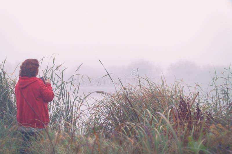 Kobieta fotograf fotografuje mgłę na jeziorze fotografia royalty free