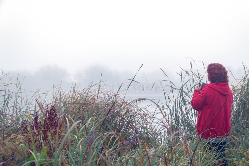 Kobieta fotograf fotografuje mg?? na jeziorze obraz royalty free
