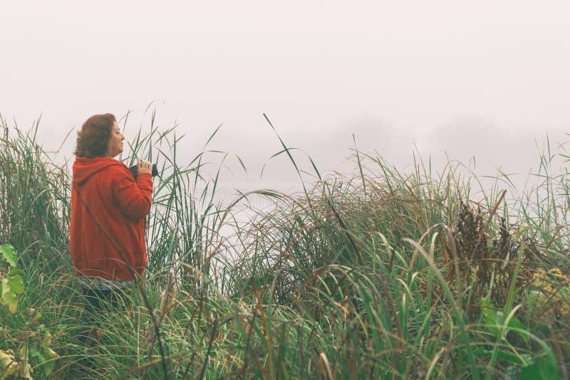 Kobieta fotograf fotografuje mg?? na jeziorze obraz stock
