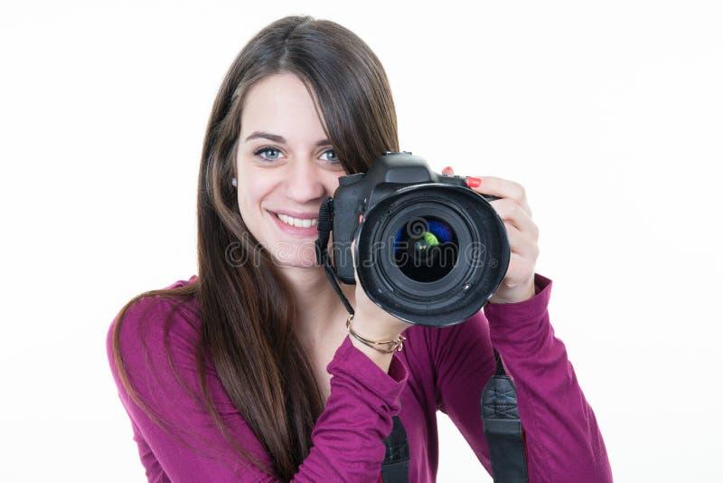 Kobieta fotograf z cyfrową SLR kamerą w biały tła ono uśmiecha się zdjęcie stock
