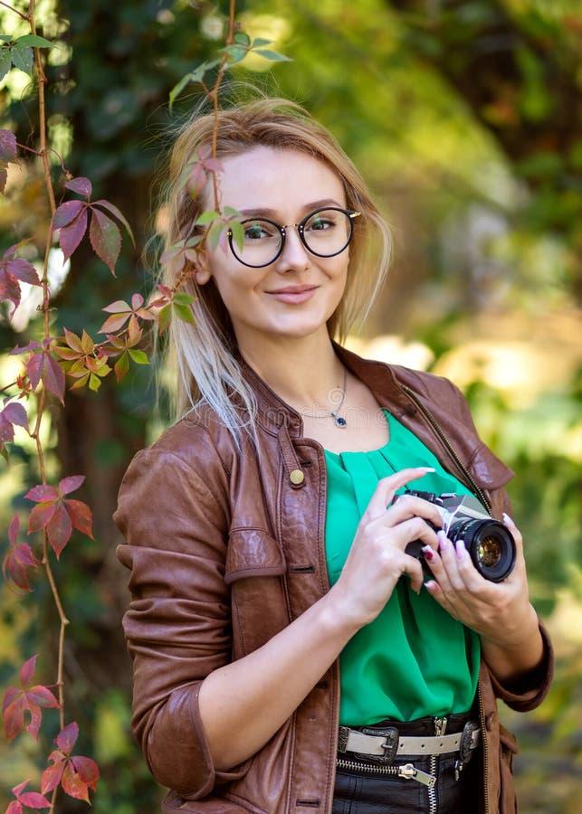 Kobieta fotograf z modnisia stylu szkłami bierze obrazki w parku z retro kamerą zdjęcia stock