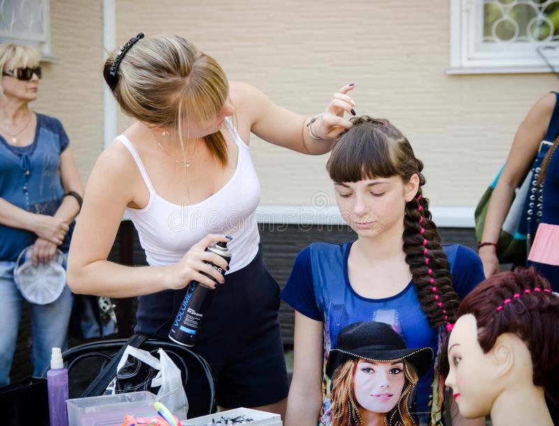 Kobieta fryzjer robi fryzurze dla dziewczyny przy miasta przyjęciem zdjęcie stock