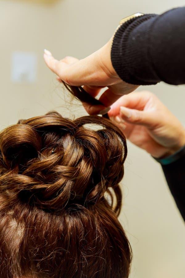 Kobieta fryzjer robi fryzurze używać fryzowania żelazo dla długie włosy młoda kobieta fotografia stock