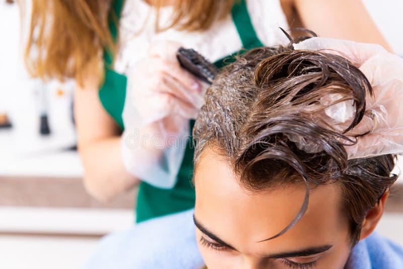 Kobieta fryzjer stosuje barwidło mężczyzny włosy zdjęcia royalty free