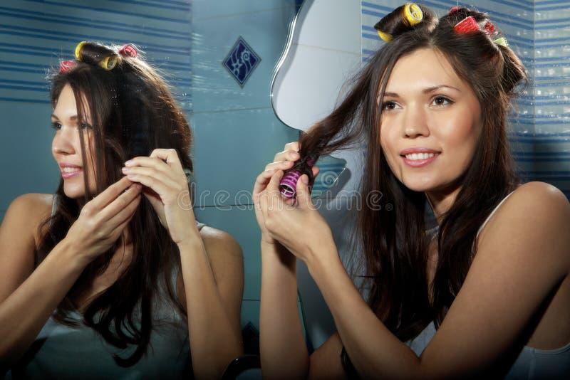 Kobieta fryzuje jej włosy zdjęcie stock