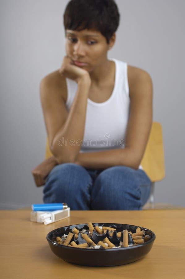 Kobieta Gapi się Przy Pełnym Ashtray papierosy Na stole obraz stock