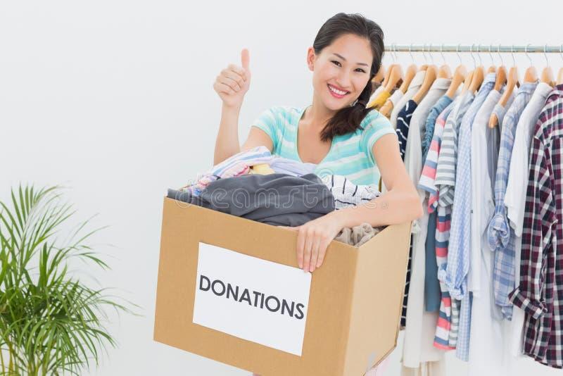 Kobieta gestykuluje aprobaty z odzieżową darowizną zdjęcia royalty free