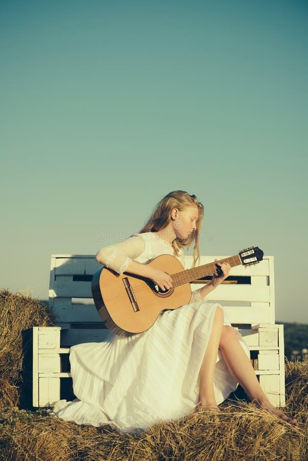 Kobieta gitarzysta wykonuje muzyka koncert Fasonuje muzyka w biel sukni na pogodnej naturze Albinos dziewczyny chwyta gitara akus zdjęcie stock