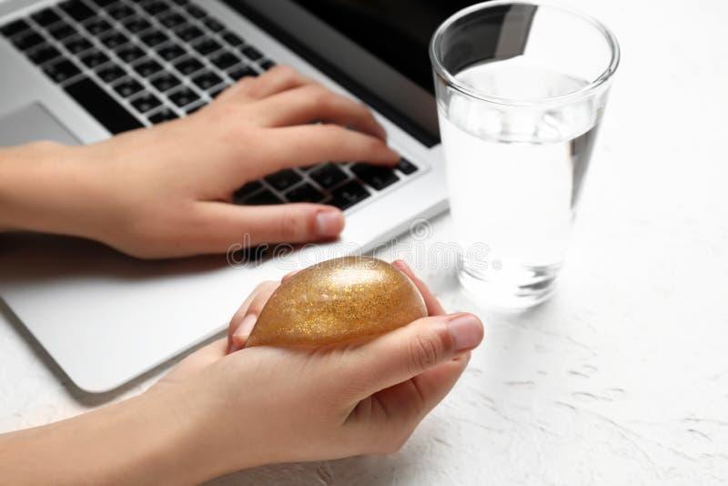 Kobieta gniesie stres piłkę podczas gdy pracujący z laptopem fotografia stock