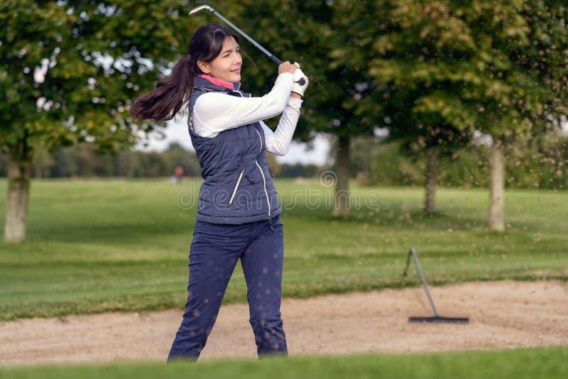 Kobieta golfista bawić się z piaska bunkieru fotografia royalty free