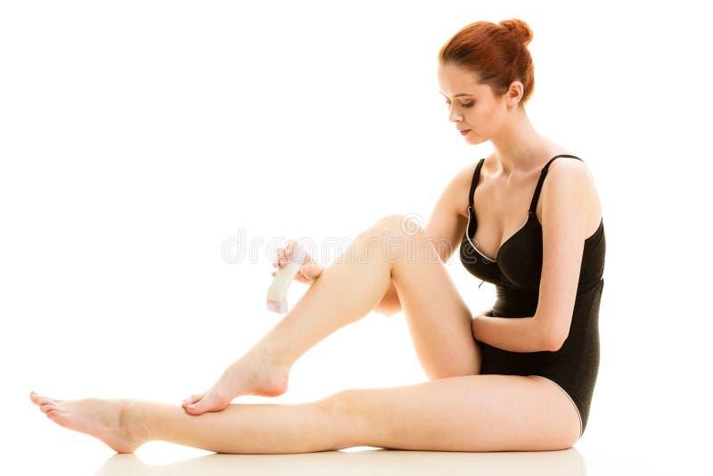 Kobieta goli ona nogi z elektryczną żyletką fotografia stock