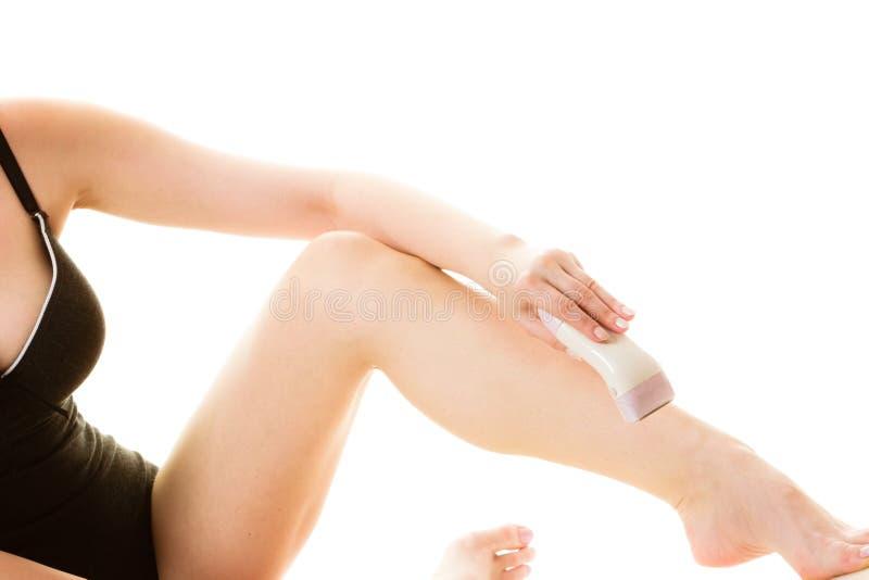 Kobieta goli ona nogi z elektryczną żyletką zdjęcie royalty free