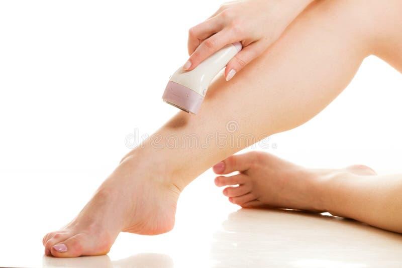 Kobieta goli ona nogi z elektryczną żyletką obrazy royalty free