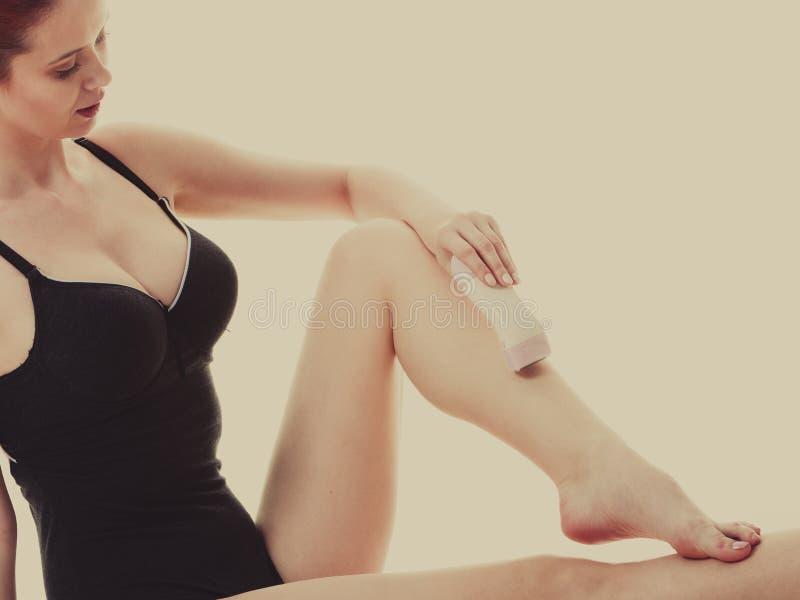 Kobieta goli ona nogi z elektryczną żyletką zdjęcie stock