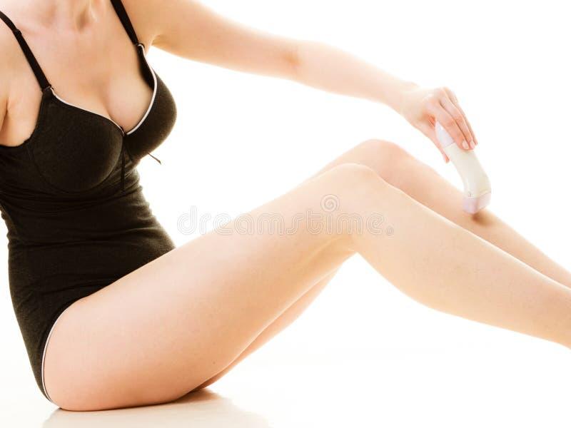 Kobieta goli ona nogi z elektryczną żyletką zdjęcia royalty free