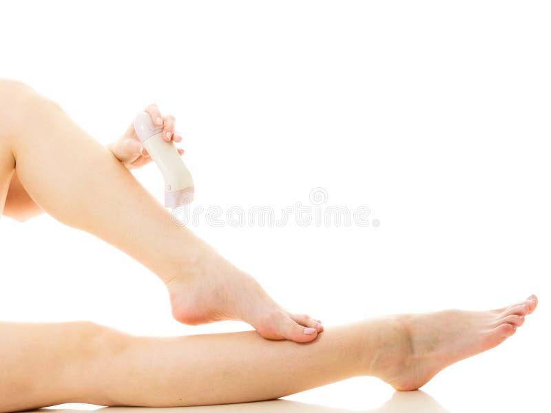 Kobieta goli ona nogi z elektrycznym depilatorem obraz stock