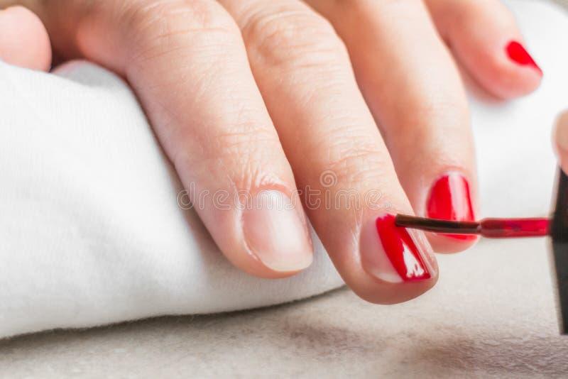Kobieta gwoździe robiący manikiur z czerwonym gwoździa połyskiem zdjęcia stock
